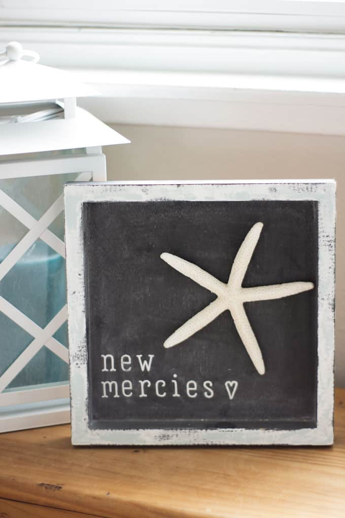 chalkboard sign with starfish and lantern in background