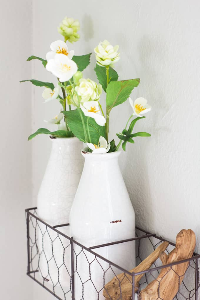 create temporary accent wall mill bottle in racks with flowers and driftwood