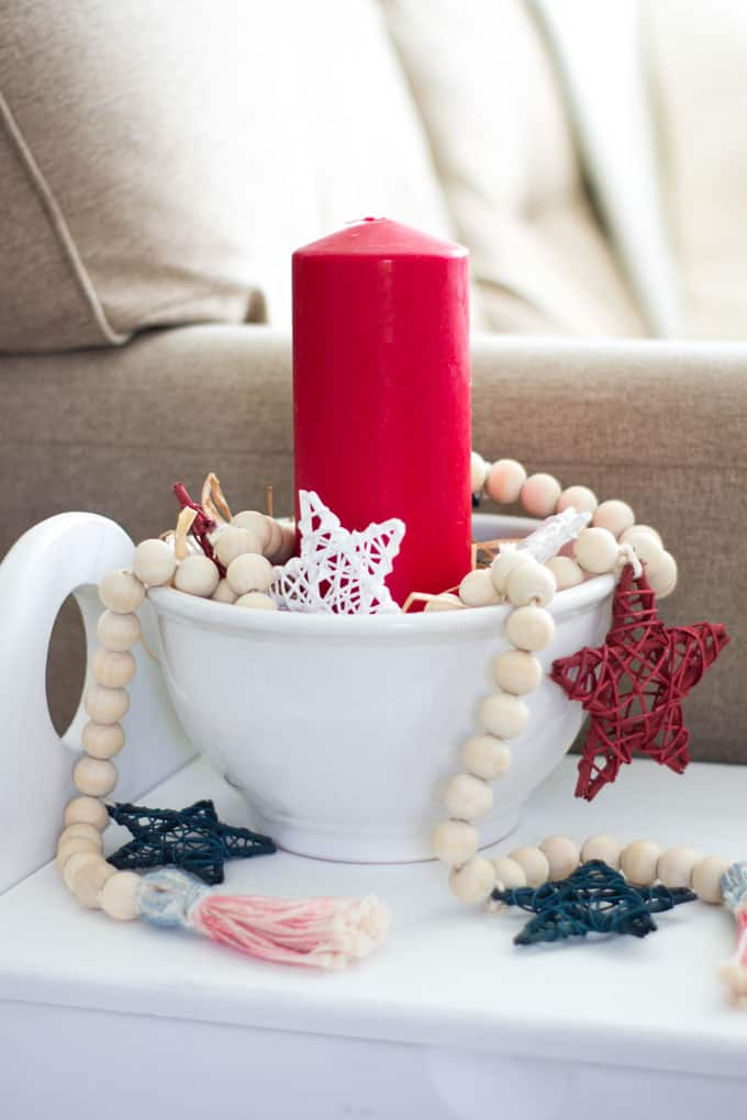 diy wood bead garland with stars white bowl with red candle and wood bead garland with red white blue stars on white table