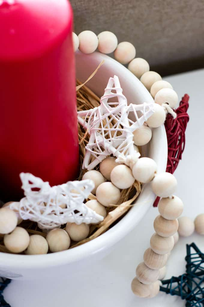 diy wood bead garland stars in white bowl with red candle