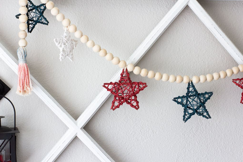 diy wood bead garland with stars hung on wall with window pane
