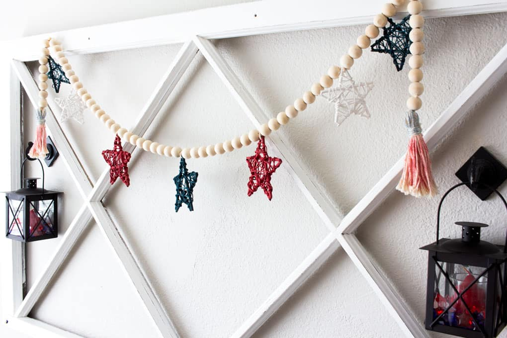 diy wood bead garland with stars hung on wall with window pane and black lanters