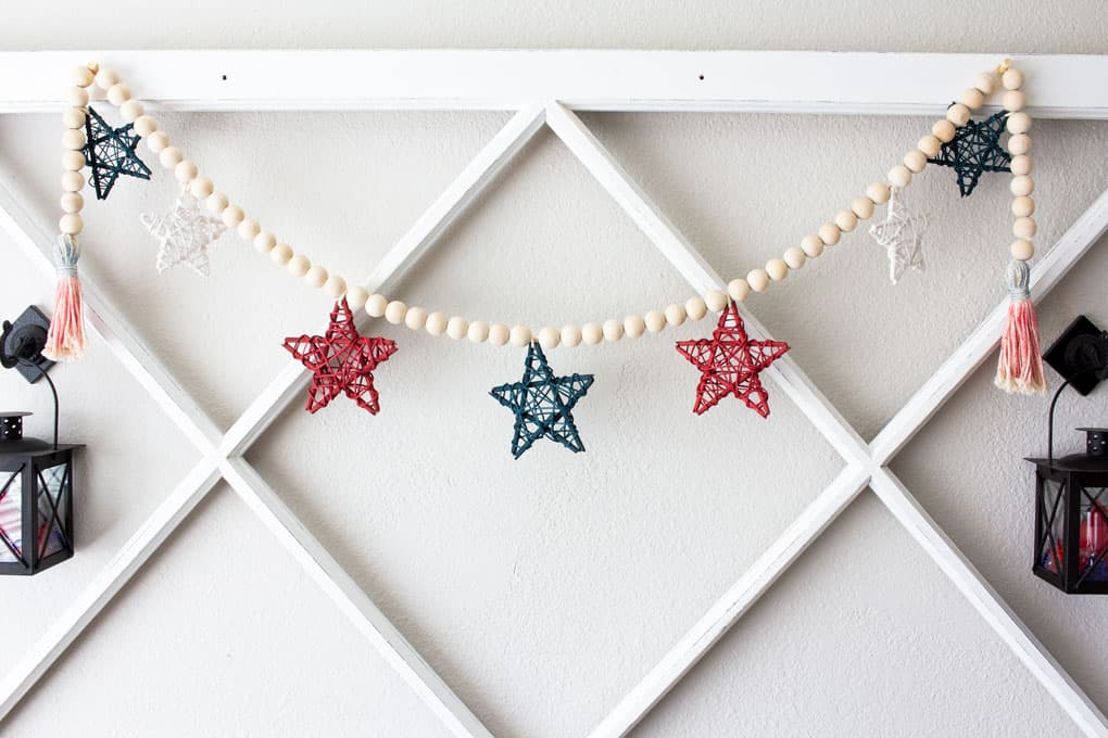 diy wood bead garland with stars hung on wall with window pane and black lantern
