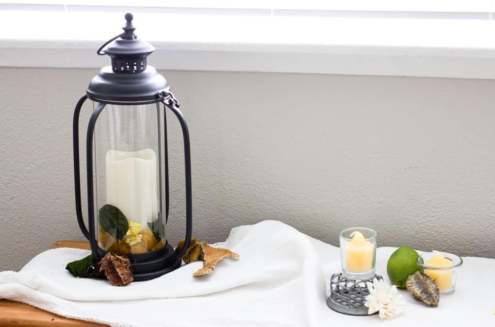 black lantern with candles and natural elements
