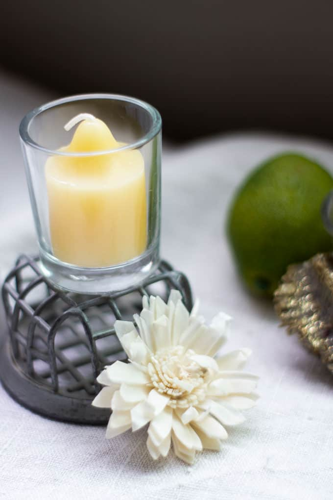 yellow votive candles with dried flowers on linen cloth