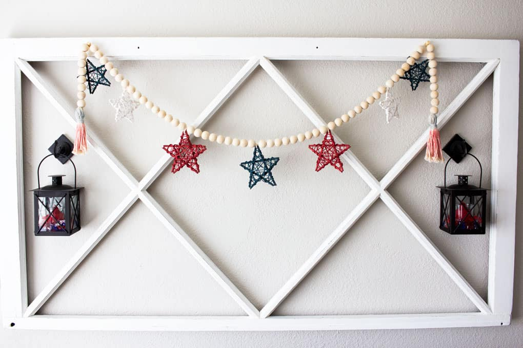 wood bead garland with stars window pane and lantern on wall