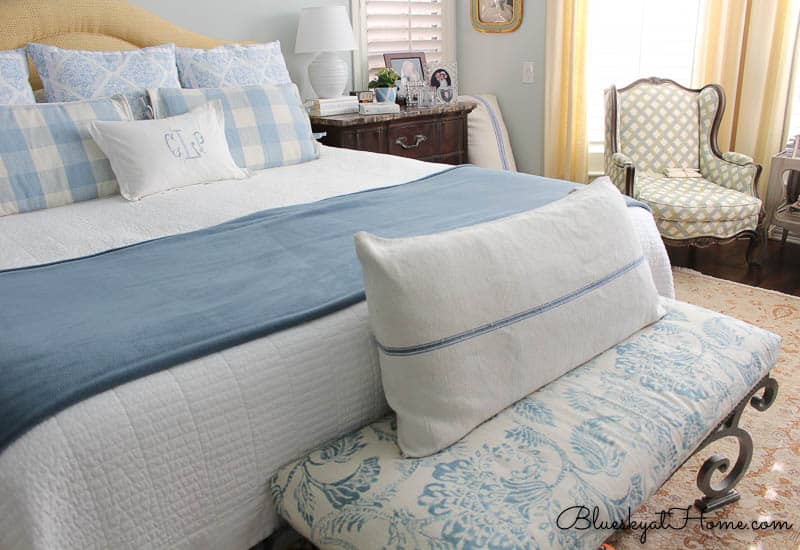 summer bedroom in blues and whites with bench at foot of the bed