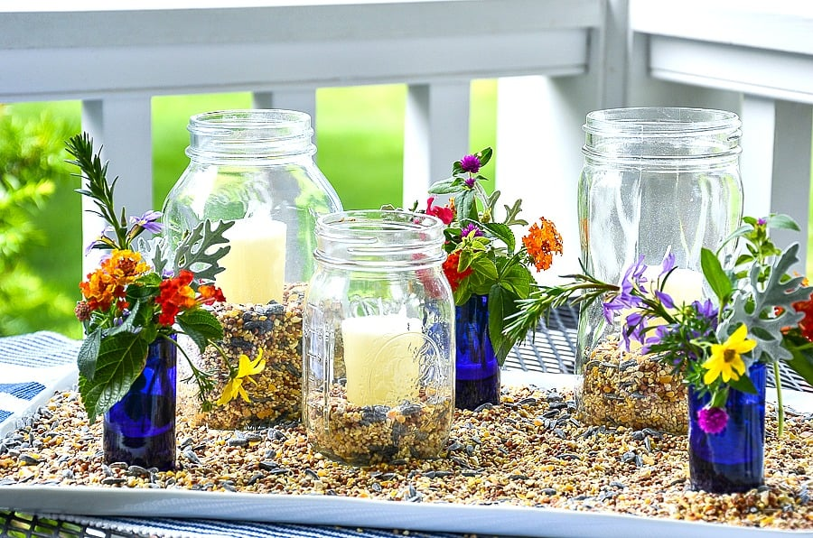 mason jars with candles outside on a tray with vases of flowers