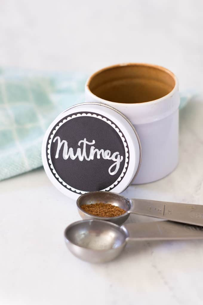 space saving spice storage nutmeg labeled spice tin on counter with measuring spoons and towel