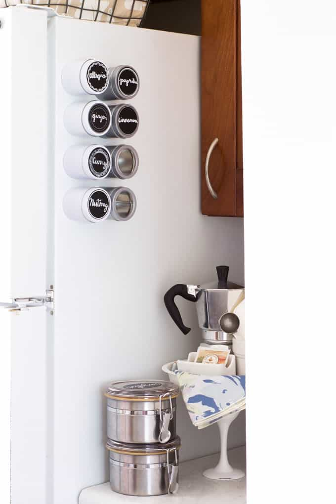 space saving spice storage refrigerator with spice tins and coffee station next to it
