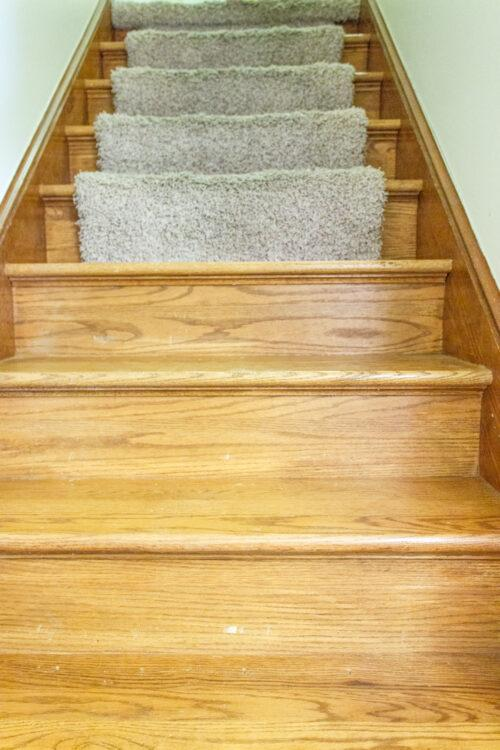 staircase with half carpet and half bare wood