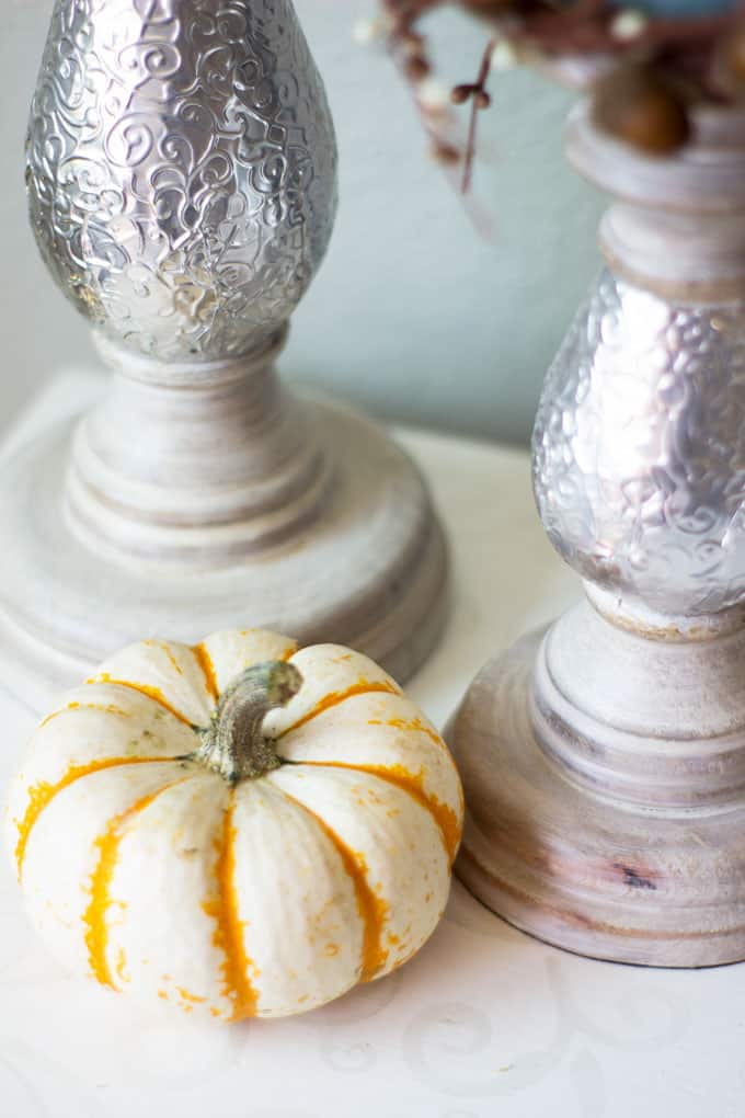 small home fall tour candlesticks and pumpkin on white surface