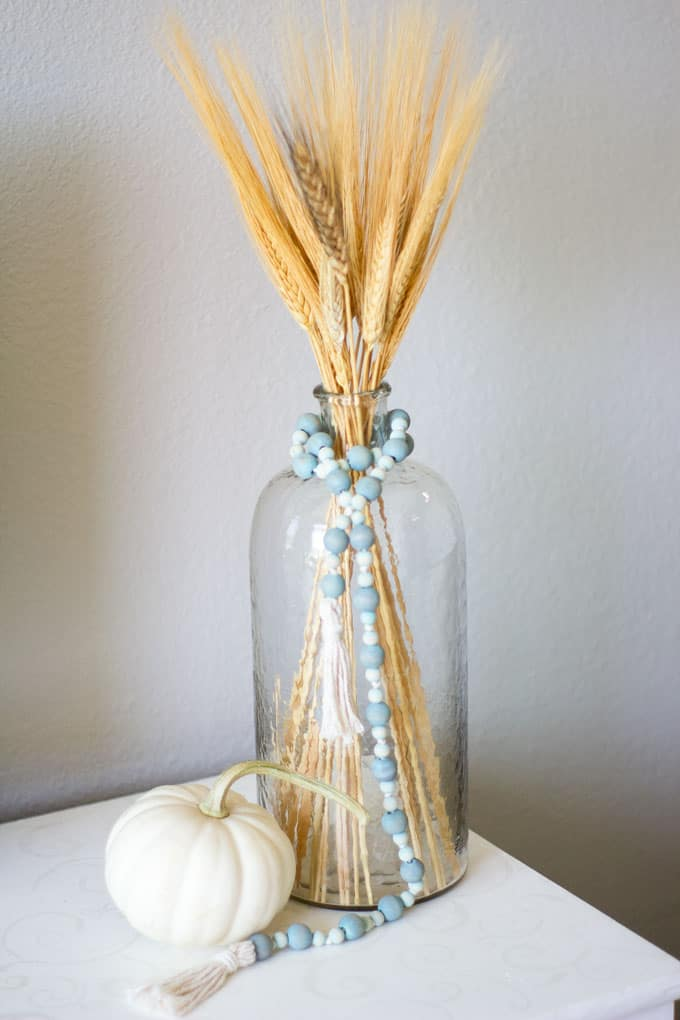 small home fall tour glass vase with wheat and wood bead garland and pumpkin on white surface