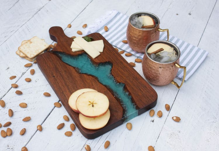 tuesday turn about 17 colorful inspiration cutting board with resin middle on shiplap surface with copper mugs and apple slices