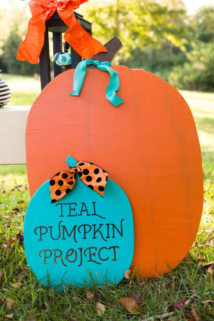 teal and orange pumpkin stands with Teal Pumpkin Project written on it