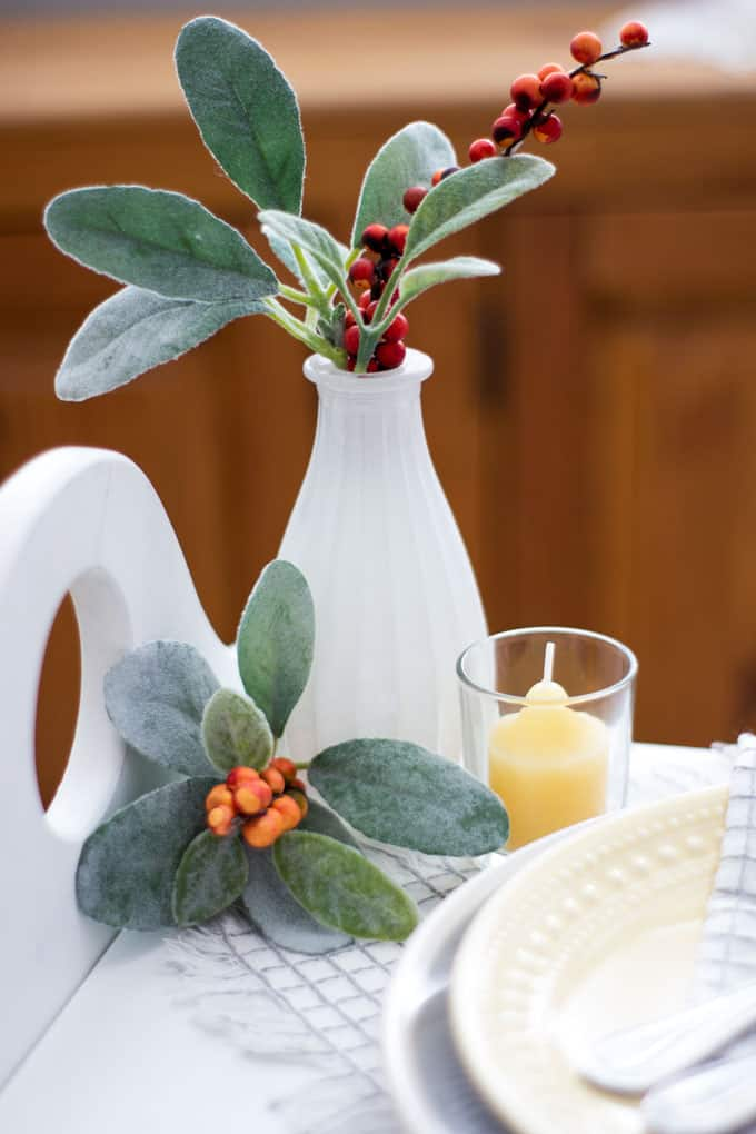 white vase with greenery and berries and yellow candle on white surface