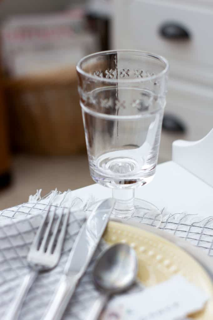 pretty stemware on white surface with table setting