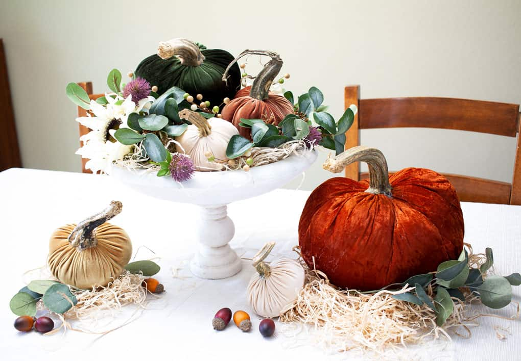 thanksgiving centerpiece with velvet pumpkins straw and acorns and faux florals on a table