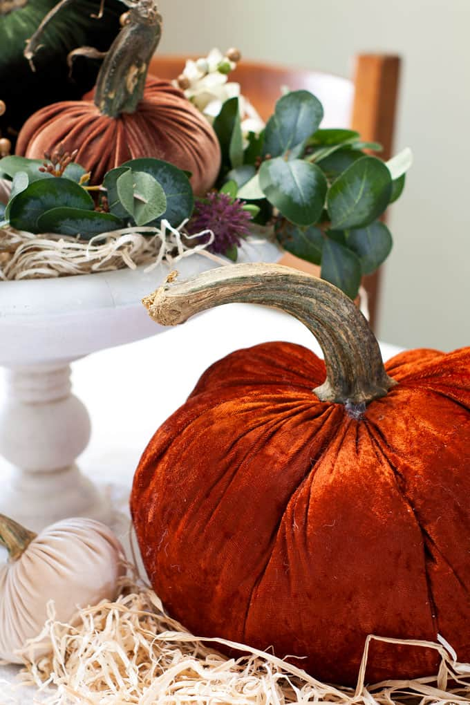 large orange velvet pumpkin with real stem on table with straw and acorns