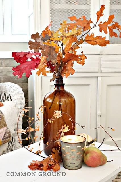 tuesday turn about 21 fall home tours fall amber glass vase with leafy branches on white table with fall decor