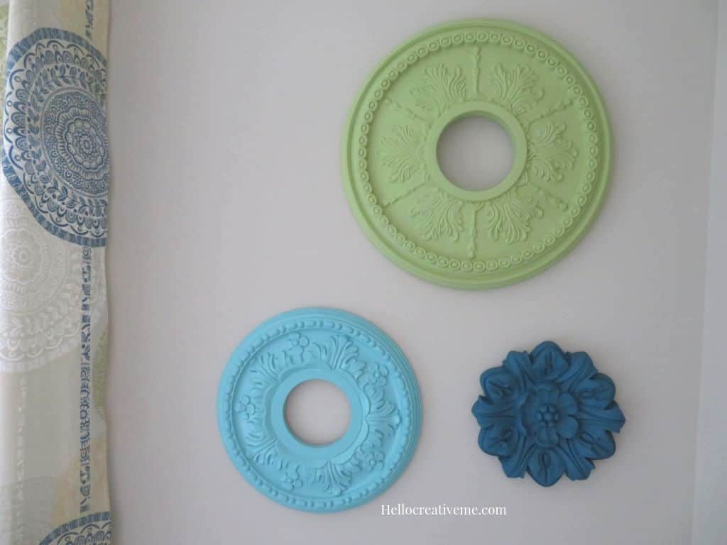 tuesday turn about 22 ceiling medallions on the wall in greens and blues