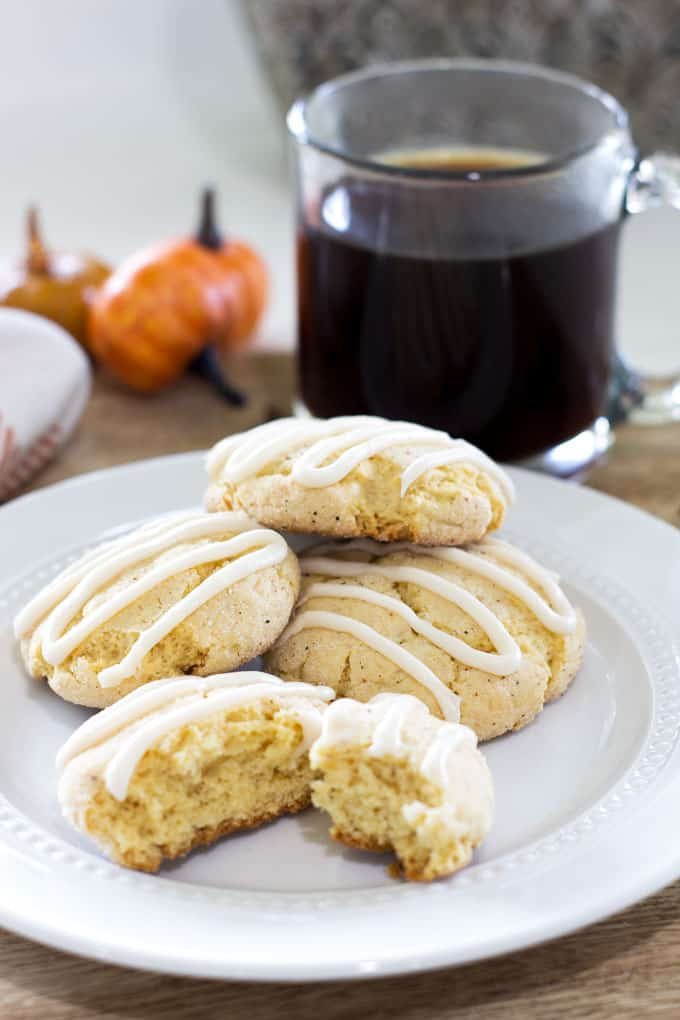 easy holiday nutmeg cookies on white plate with coffee and pumpkins in background