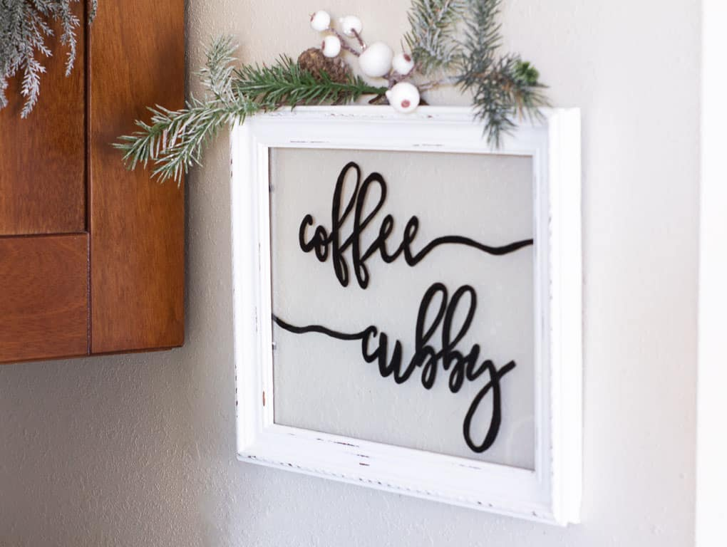 window sign that says coffee cubby with white frame and greenery