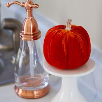 copper soap dispenser and velvet pumpkin on a cupcake plate