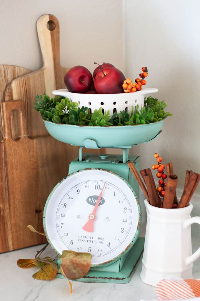 love your dark kitchen cabinets scale with apples and bread boards with pitcher and cinnamon sticks on white counter