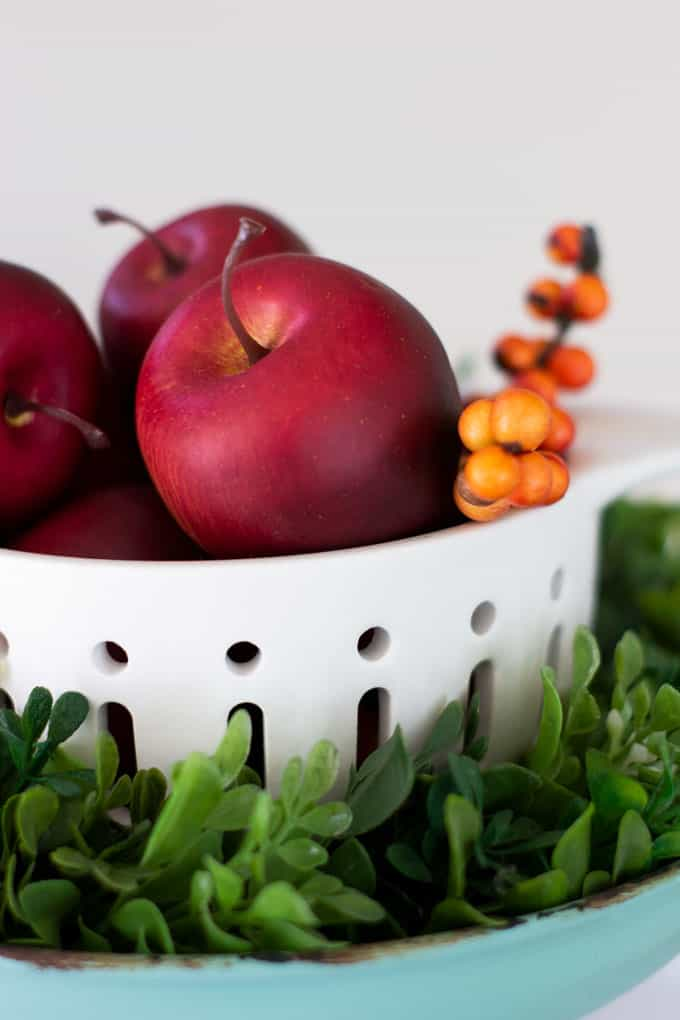 apples in a colander with berries and boxwood