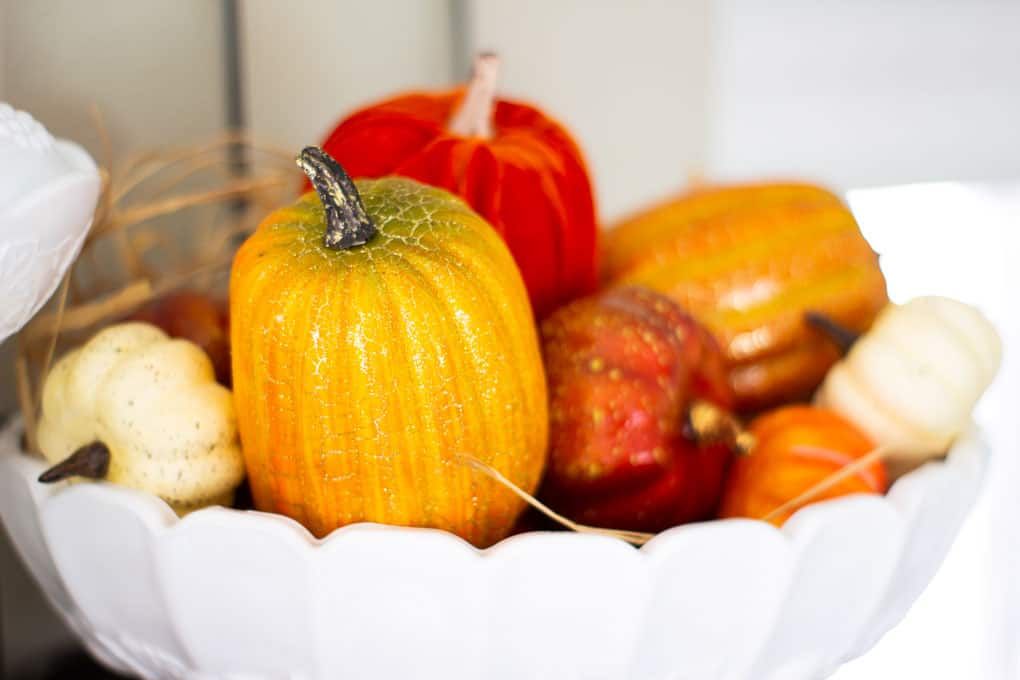milk glass bowl with faux pumpkins on open shelving
