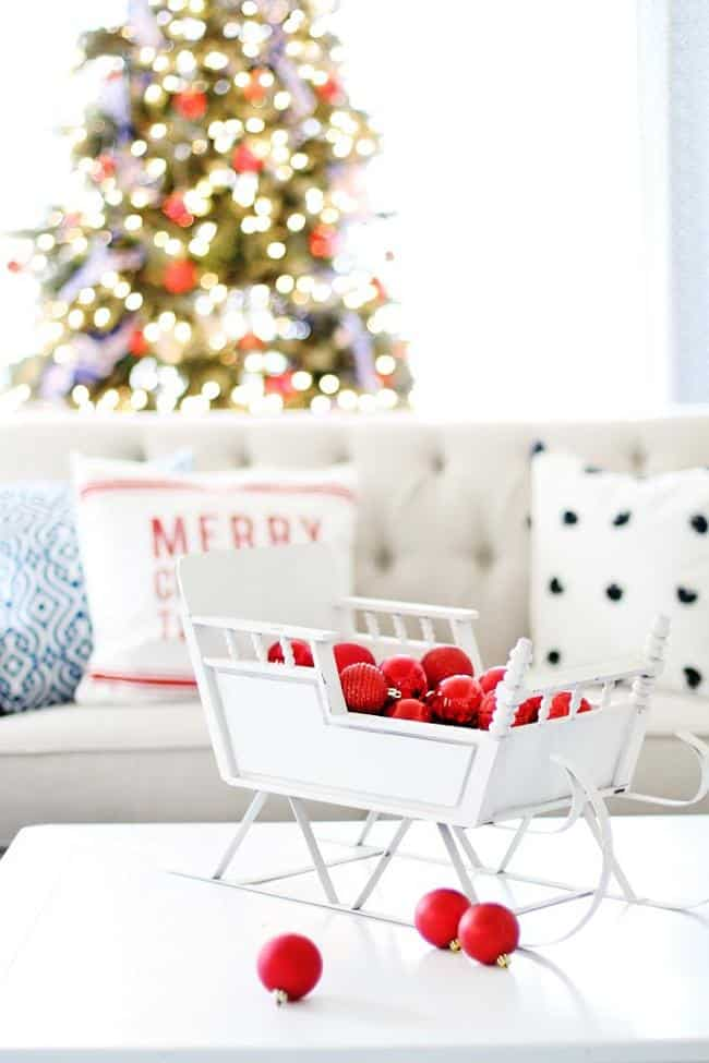 white christmas sleigh with red ornaments on coffee table