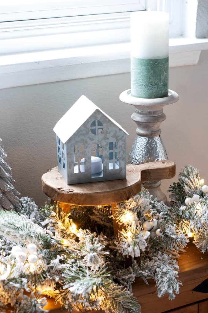 flocked garland with tea light house and candle holder on wooden surface