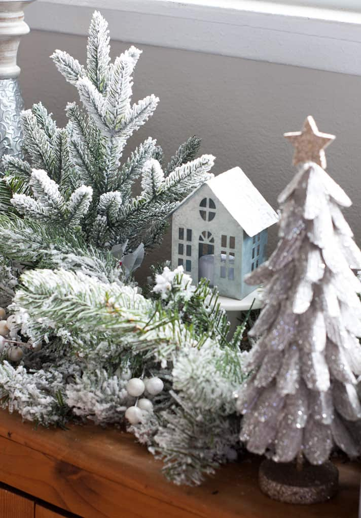 flocked garland with tea light house and candle holder and glitter tree on wooden surface