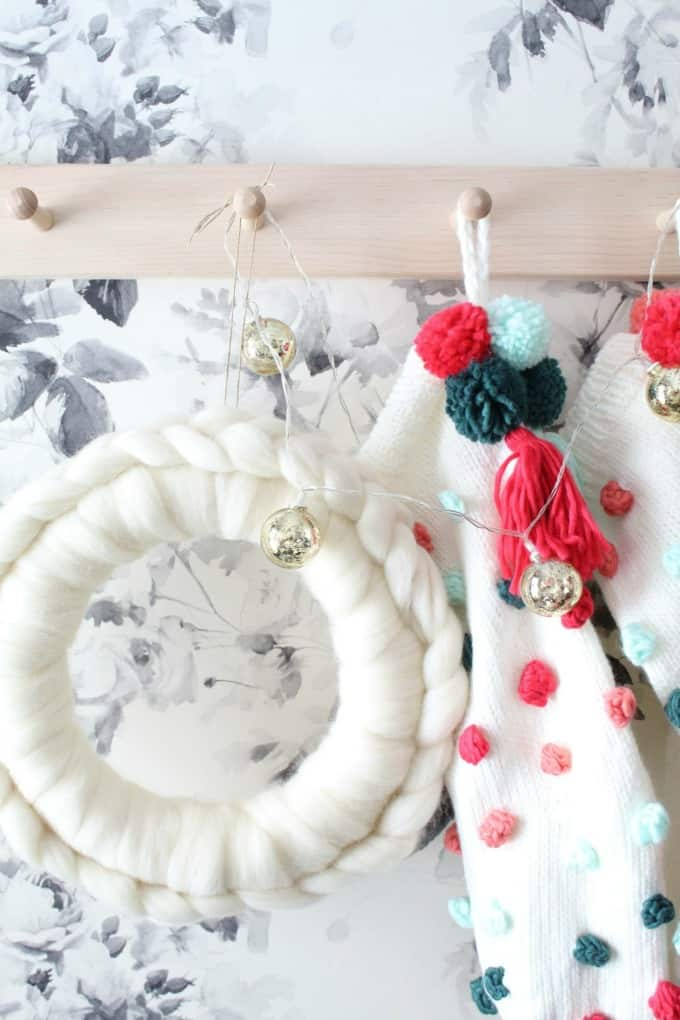 white wool wreath with pom pom garland on a coat rack