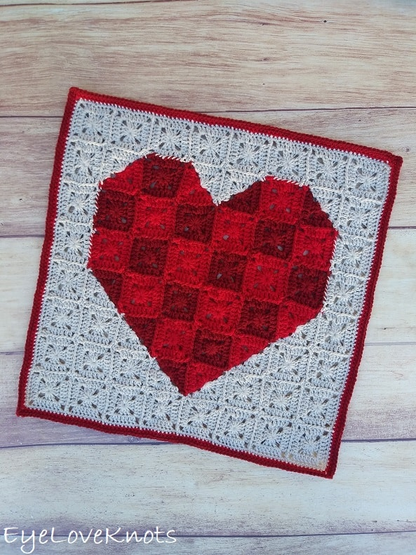 crocheted heart wall hanging on wood surface