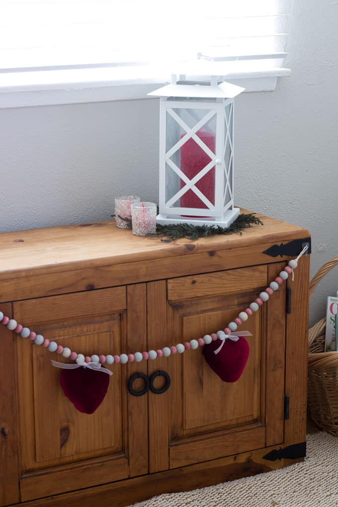 how to make a valentine garland with velvet covered hearts hanging on a wooden window bench with white lantern and votives