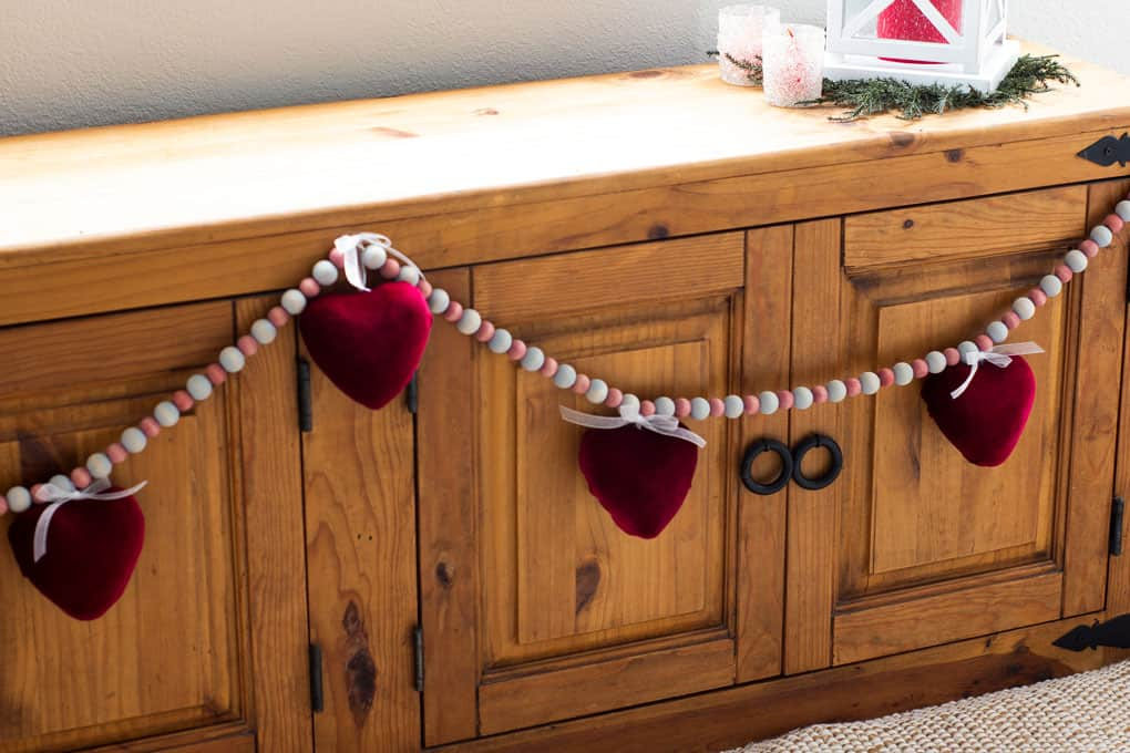 how to make a valentine garland with velvet covered hearts hanging on a wooden window bench