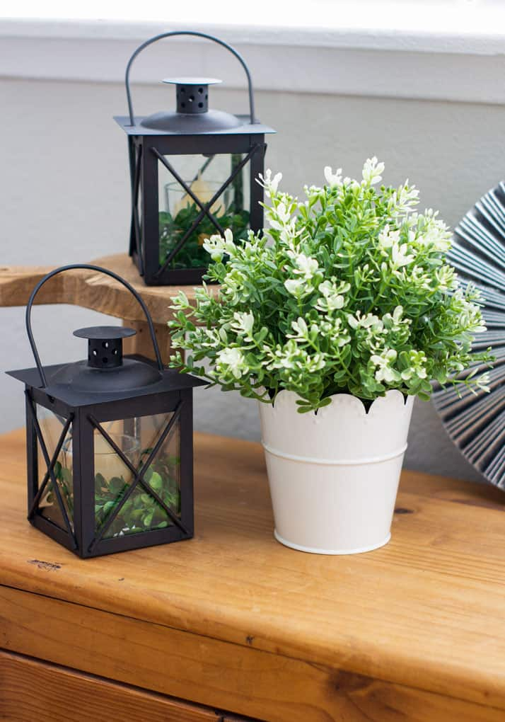 black lanterns with white pot and boxwood on wood surface