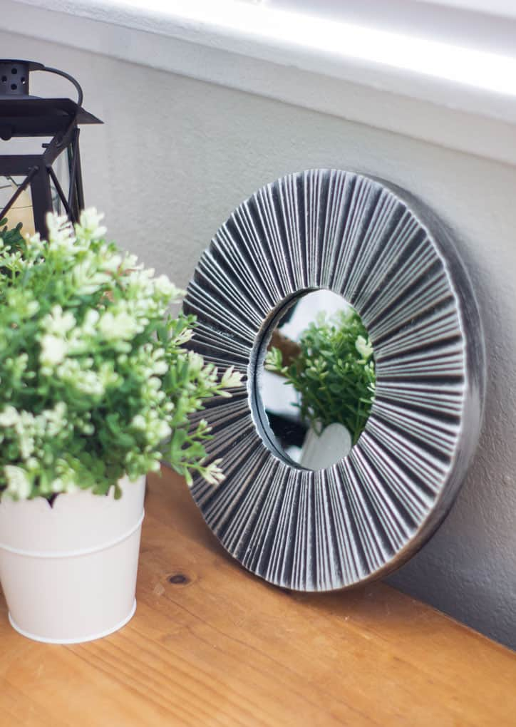 refresh your mantel with spring decor round black and silver mirror on wood surface