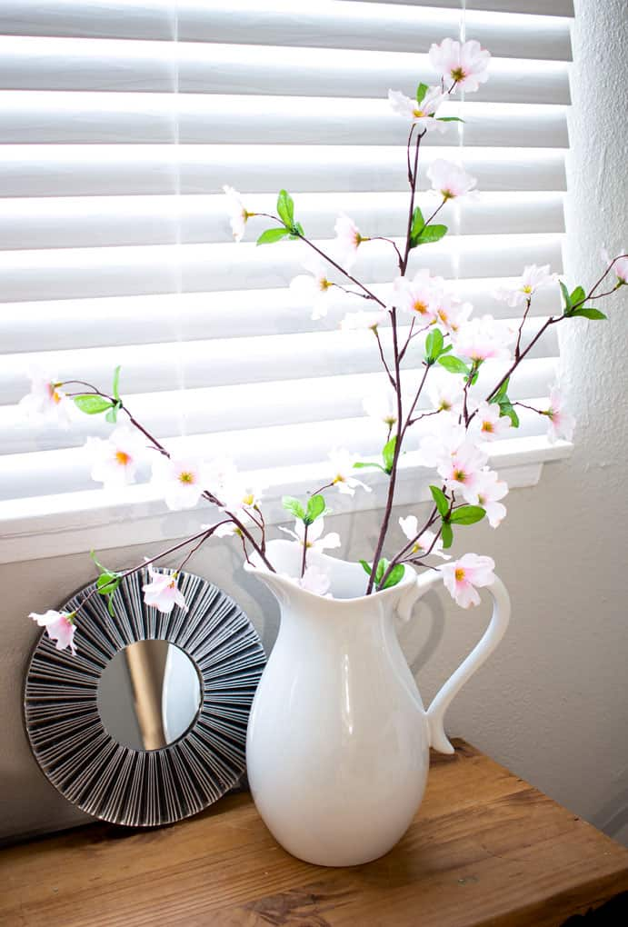 refresh your mantel with spring decor white pitcher with pink blossoms and mirror on window bench