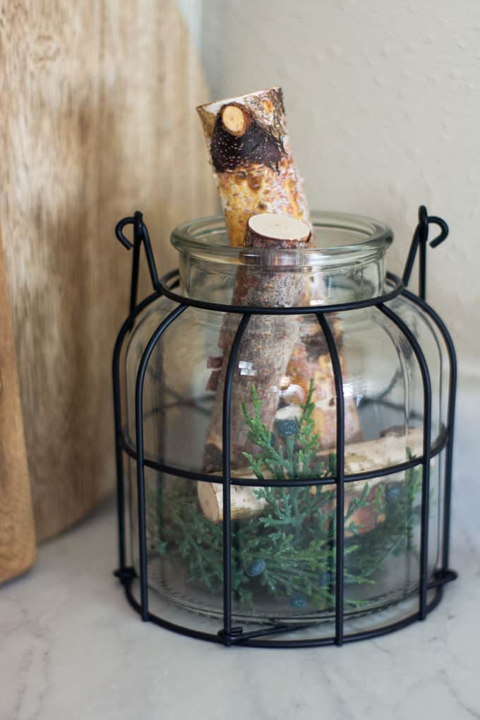 love your dark kitchen cabinets with winter neutrals wire lantern with greenery and birch logs