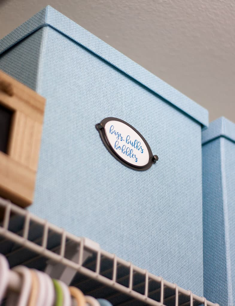 blue textured box on closet shelf with label and metal handle