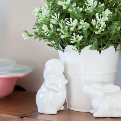 spring decor picks for your home faux boxwood with white ceramic bunnies on wood shelf