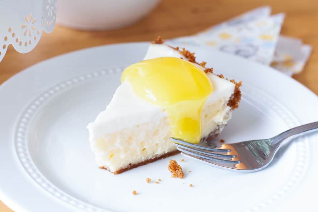 best lemon cheesecake slice on plate with lemon curd on top