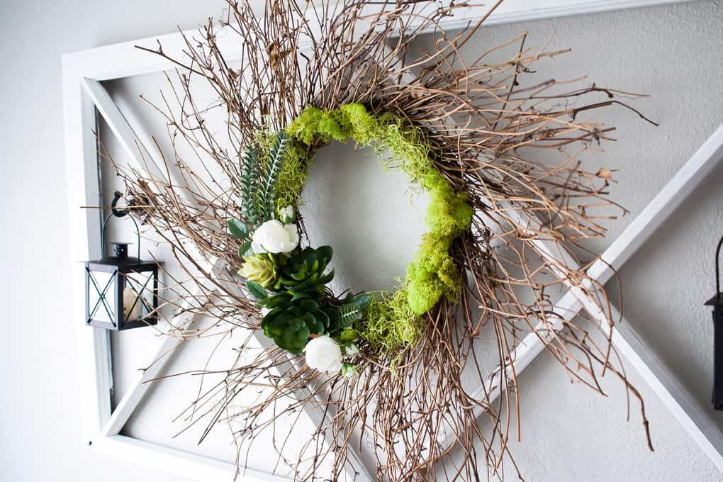 early spring succulent wreath on window pane with black lantern