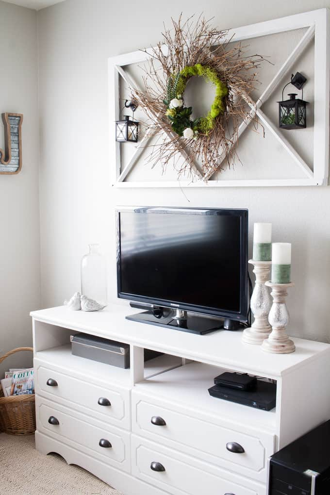 easy early spring wreath hanging on window pane above media console