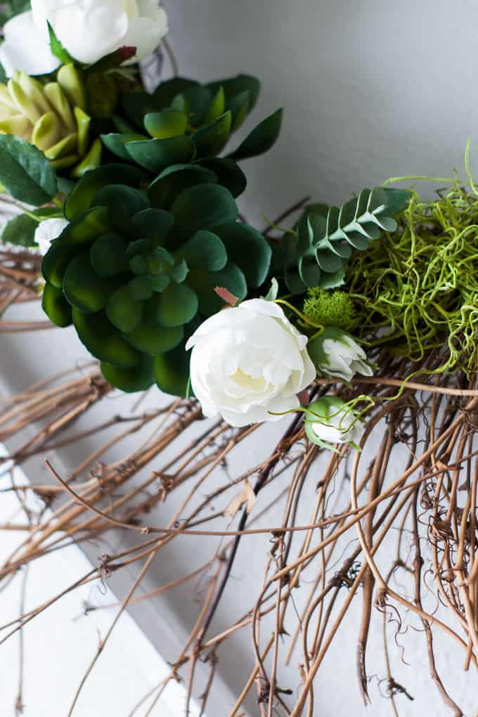 succulents and white peonies against a grapevine spray