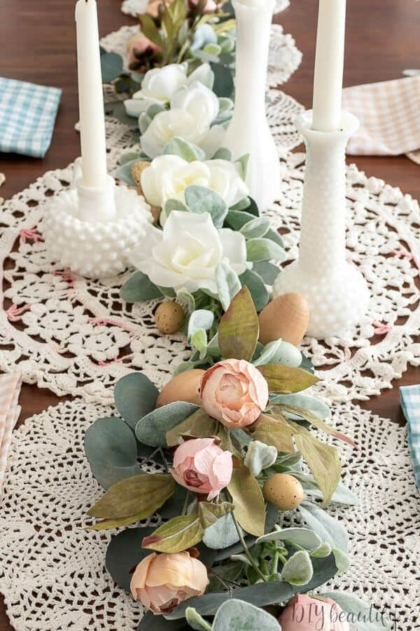 floral runner with milk glass vases on doilies