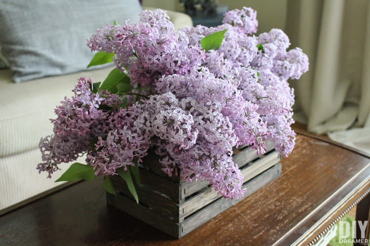 crate with lilacs on wood surface